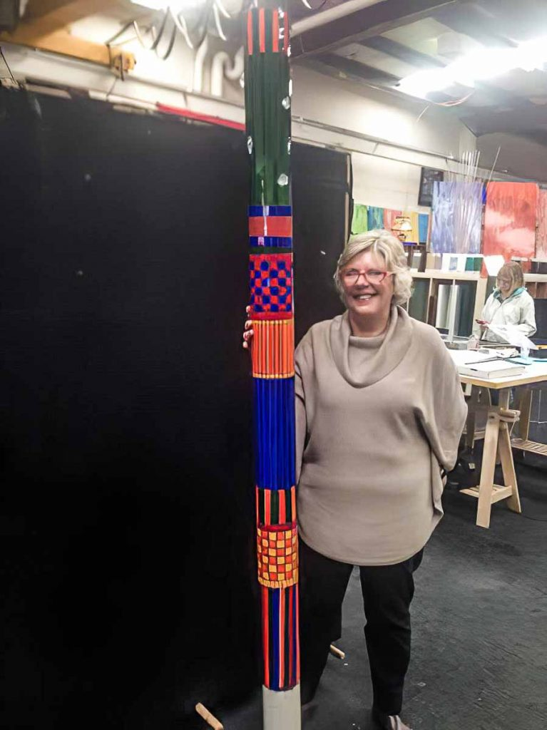 Artist: Elizabeth White with her completed mosaic totem pole. Monday afternoon mosaic classes at The Glass Emporium